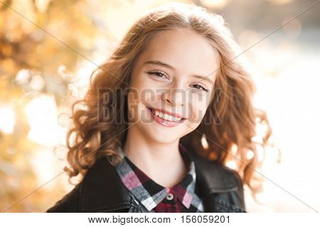 Laughing teen girl 12-14 year old posing outdoors over nature background. Looking at camera. Childhood.