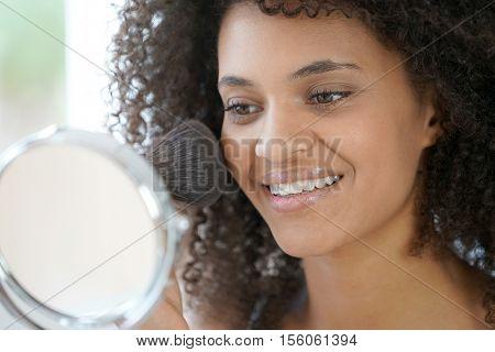 Beautiful mixed-race woman putting makeup on
