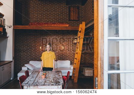 Portrait of an attractive young blonde woman smiling while standing behind a table her modern loft apartment