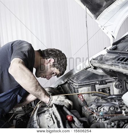auto mechanic repairing a car engine. Space for text.