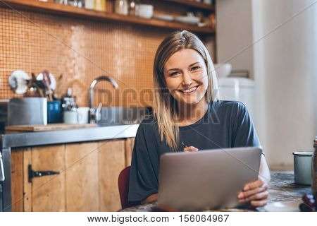 Portrait of an attractive young blonde woman sitting at a table in her kitchen using a digital tablet while eating breakfast