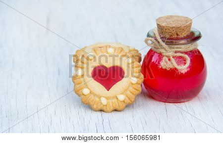 Cookies with jelly in the shape of a heart and the magic elixir of love. Romantic concept. Aphrodisiac and Love Potion. Copy space.