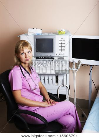 Portrait of female doctor near ultrasound equipment at modern clinic.