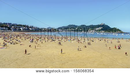San Sebastian Spain - August 22 2016: Watches on the beach promenade of La Concha in San Sebastian in a sunny day on August