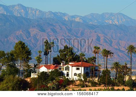 Spanish style Villa Mansion surrounded by Palm Trees on top of a hill with amazing views taken in Los Angeles area