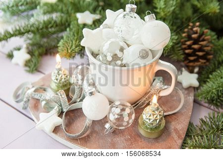 White mug with glittery christmas baubles with pine branches