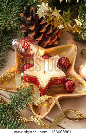 Burning candle and glittery christmas decorations with pine branches