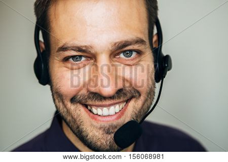 Confident male operator. Portrait of handsome young male operator in headset looking at camera and smiling while standing against white background