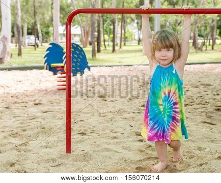 Young girl in sand on playground equipment at park