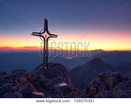 Steel Crucifix At Mountain Peak In Alps. Sharp Rocky Summit, Daybreak Sun In Sky.