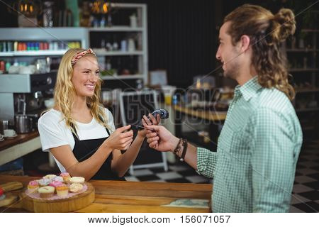 Happy customer giving credit card to waitress in café