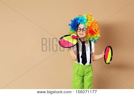 Blithesome Children. Portrait Of Happy Clown Boy Wearing Large Neon Coloured Wig