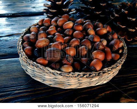 Autumn. Autumn gifts. Autumn harvest. Nuts. Cones. Nuts in a basket. Nuts on the table