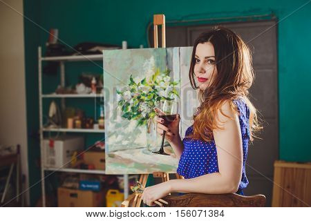 Creative Pensive Painter Girl Paints A Colorful Picture On Canvas With Oil Colors In Workshop.