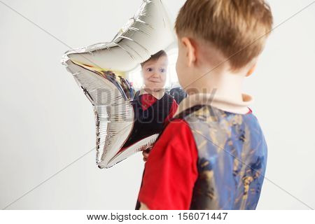 Child Laughing Looking At The Reflection In A Distorted Mirror