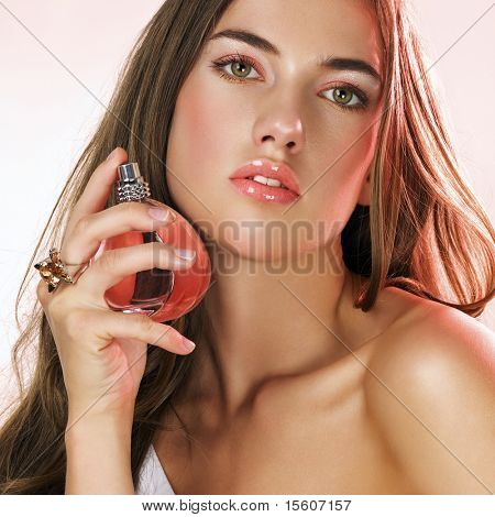 Woman with long hair applying perfume on her hair
