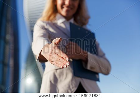 Smiling young business woman holds out an open hand ready for handshake. Partnership, business, agreement concept