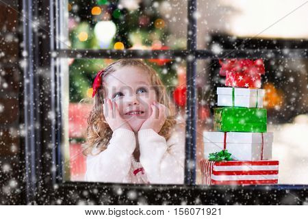 Little girl waiting for Santa at home window on Christmas eve. Kids opening Xmas presents. Child under Christmas tree with gift boxes. View from outside. Winter snowy day at home.