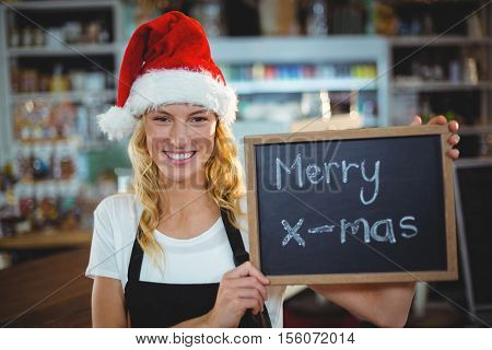 Portrait of smiling waitress showing chalkboard with merry x-mas sign in cafe