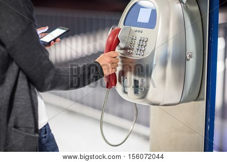 Beautiful young woman using a public phone in an airport