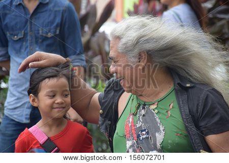 KUALA LUMPUR, MALAYSIA - DECEMBER 31, 2015 - Unidentified malaysian man caressing his niece after playing music on the street