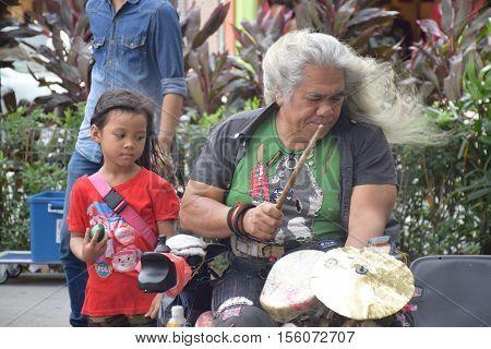KUALA LUMPUR, MALAYSIA - DECEMBER 31, 2015 - Unidentified malaysian man with his niece playing music on the street