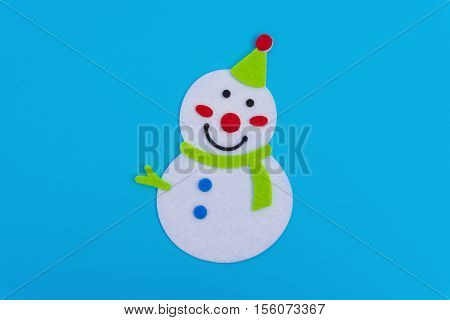 flat smiling toy christmas snowman with green scarf on blue