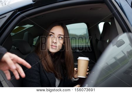 Beautiful young brunette woman with long hair and brown eyes going to get out of car. Model in warm autumn business suit holdinag coffee in hand