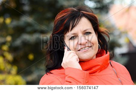 Middle aged ordinary caucasian woman with long dark hair and red jacket talking on mobile phone in park.