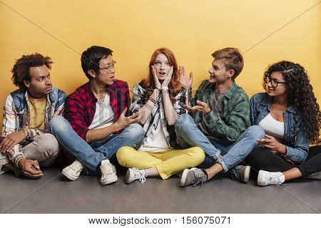 Surpsised redhead young woman sitting with her friends over yellow background