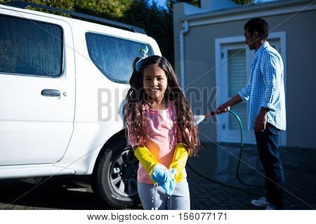 Portrait of daughter holding sponge while father doing carwash in the background
