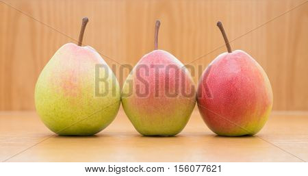three fresh pears on a wood background