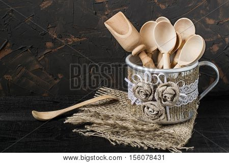 Wooden spoon and scoop in the aluminum mug with handmade decor of burlap and lace. Mug is on a napkin of burlap on dark textured background