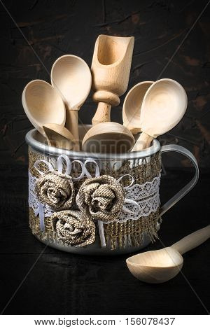 Wooden spoon and scoop in the aluminum mug with handmade decor of burlap and lace. Mug is on a napkin of burlap on dark textured background. Toned photo. Vertical