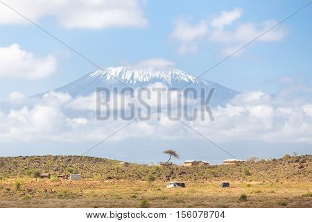 Mount Kilimanjaro, Tanzania., the highest mountain in Africa. Traditional african savannah village in foreground.