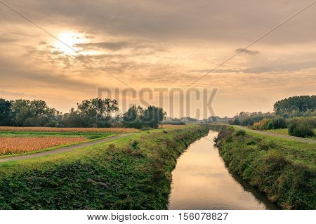 A river runs between 2 towpaths through the Flemish countryside in the autumn