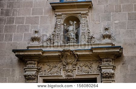 Portal decoration of a boy with cross on Alicante cathedral Saint Nicolas, Spain