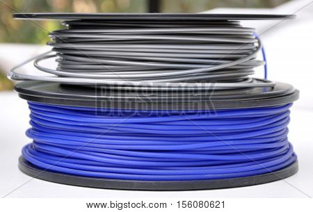 two 3d printing filament spools, silver and blue