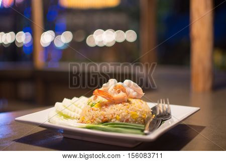 Shrimp fried rice dish is placed on a wooden table. Appetizing beautiful bokeh background blur look distinguished.