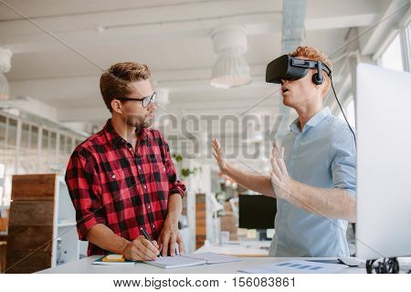 Shot of two young men testing virtual reality headset. Businessman wearing VR goggles and colleague writing notes in office.