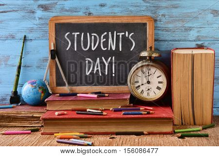 the text students day written in a chalkboard, placed on a rustic wooden school desk next to an old clock some old books, some pencils and some other school supplies