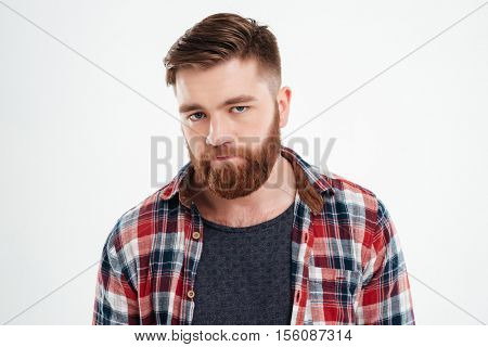 Close up portrait of disappointed bearded young man in plaid shirt over white background