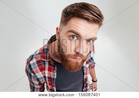 Close up portrait of a young suspecious man looking closely at camera over white background