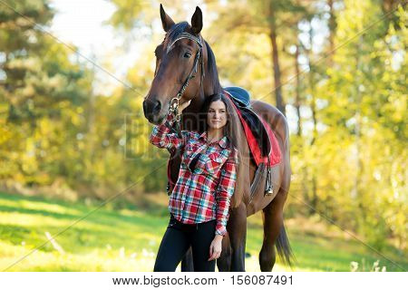 beautiful young woman with a brown horse on outdoor. Autumn landscape.