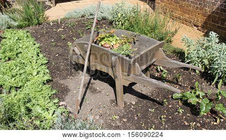 A Classic Wooden Wheelbarrow in a Vegetable Garden.