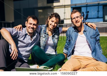 three students sitting on lawn at the university