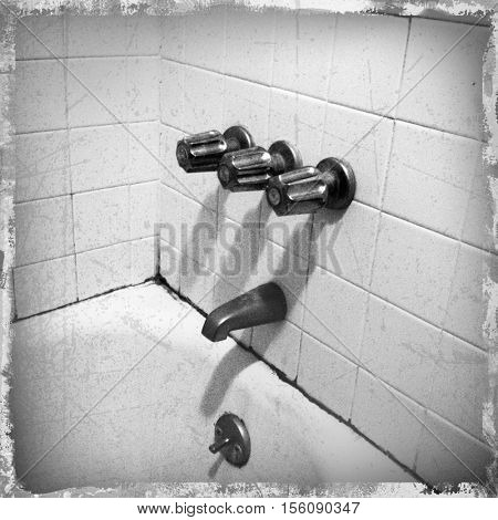 filtered black and white image of an old grungy moldy bathtub in a seedy snapshot style