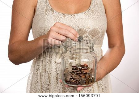 Woman puts a quarter in a clear glass savings jar for use as a financial and banking concept.