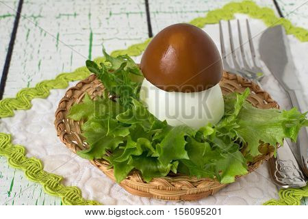 Creative idea of design of stuffed eggs in the form of porcini. Concept design of children's or festive meals. Child breakfast. Easter snack. Served on lettuce leaves. Selective focus