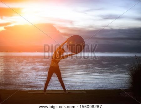 Silhouette yoga ball yung woman in the beach sunset background